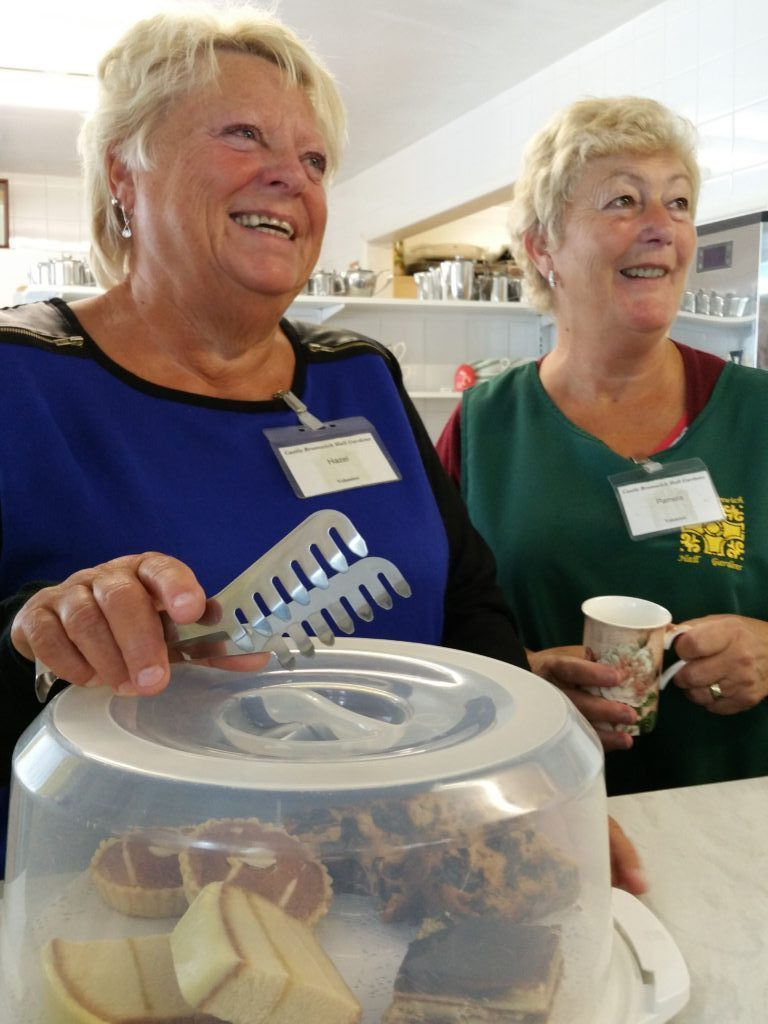two women serving in the cafe and smiling
